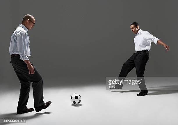 Two businessmen playing football, studio shot