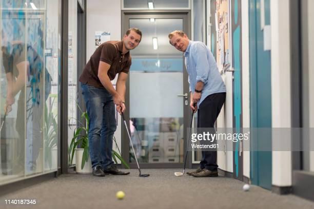 two businessmen playing golf in office - einlochen golf stock-fotos und bilder