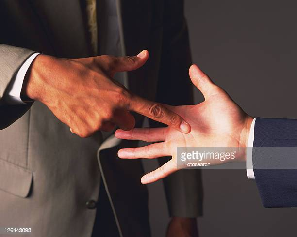 Two businessmen playing paper-rock-scissors, Side View