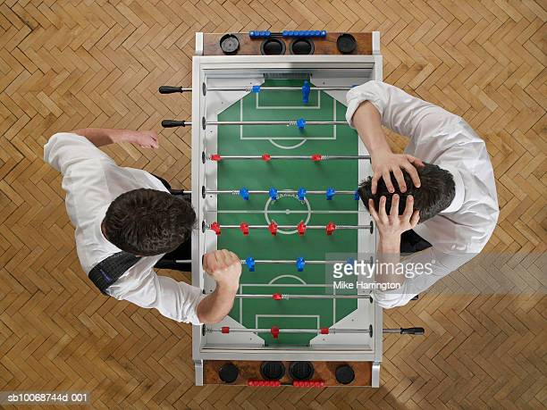 Two businessmen playing table football, overhead view