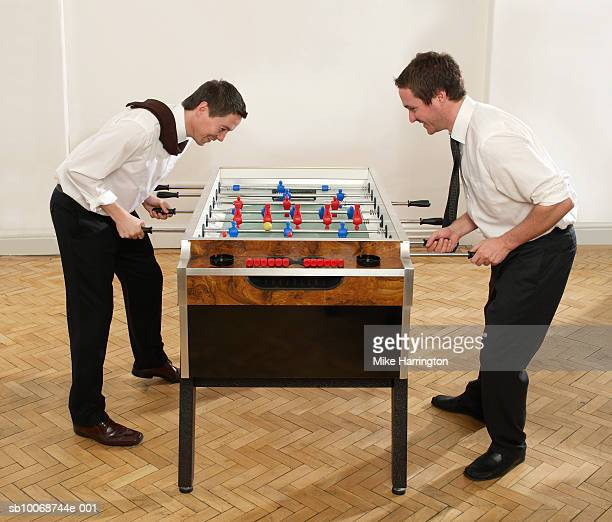 Two businessmen playing table football, side view