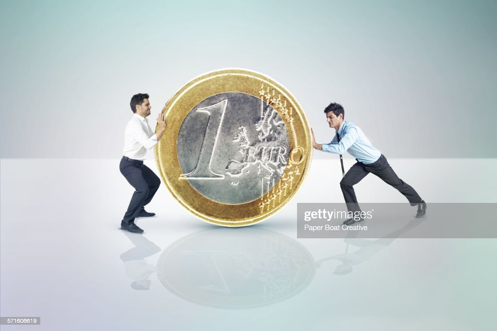 Two businessmen pushing a giant Euro coin : Stock Photo