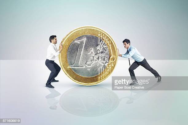 two businessmen pushing a giant euro coin - 1 euro photos et images de collection