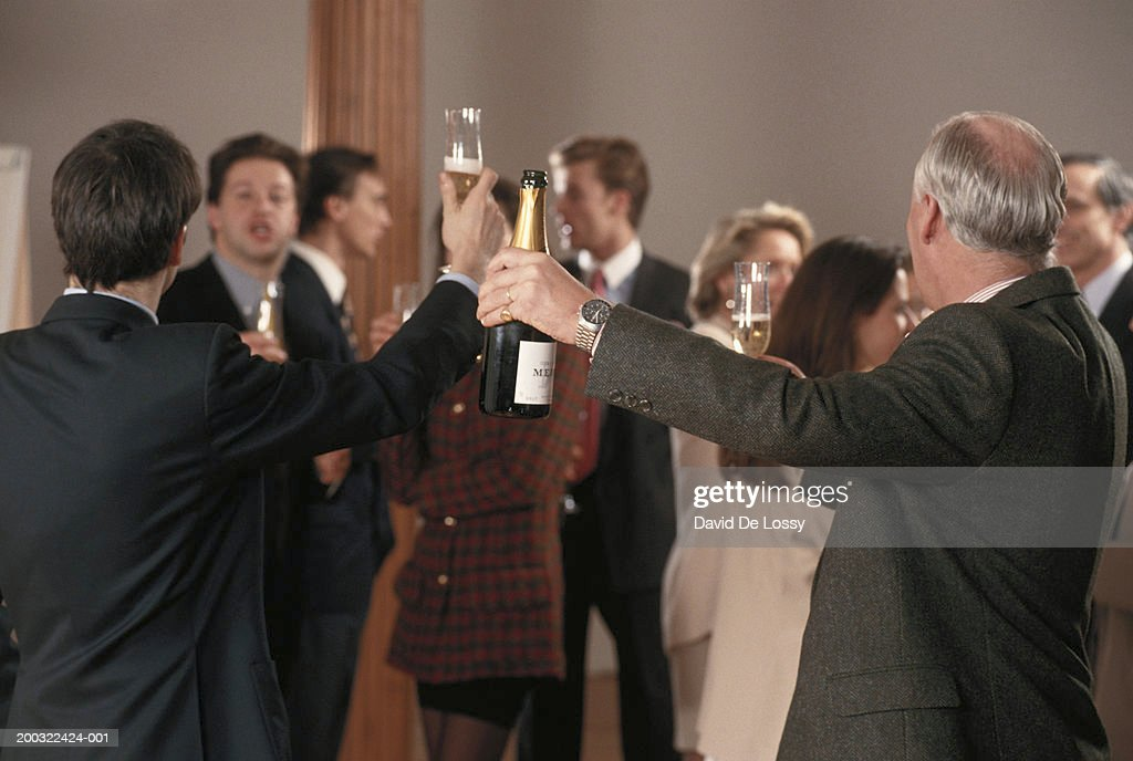 Two businessmen raising champagne : Stock Photo