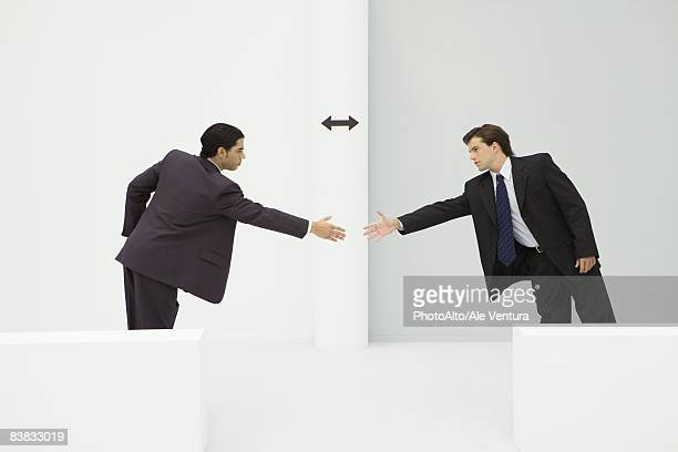 Two businessmen reaching to shake hands, arrow between them
