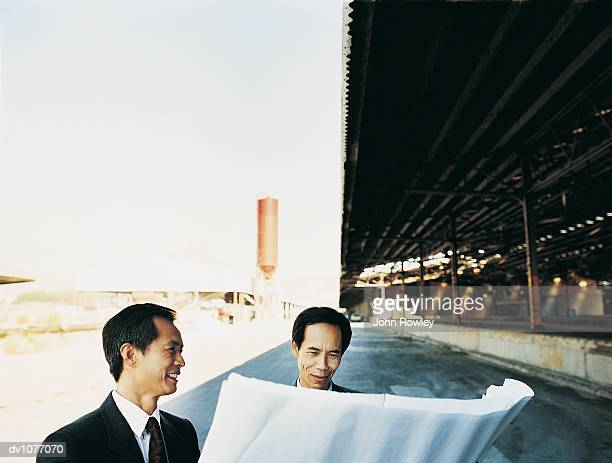 Two Businessmen Reading a Blueprint Outside a Factory Building in an Industrial Park
