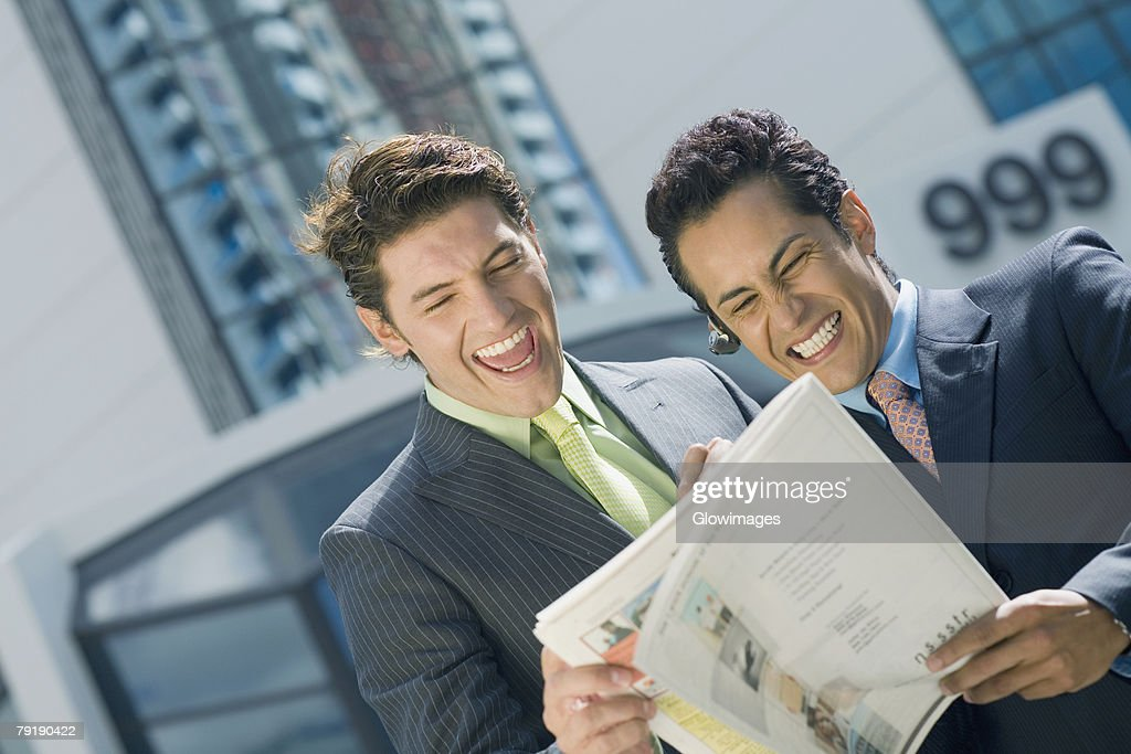Two businessmen reading a magazine and smiling : Stock Photo