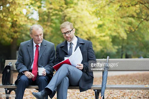 Two businessmen reading document on park bench
