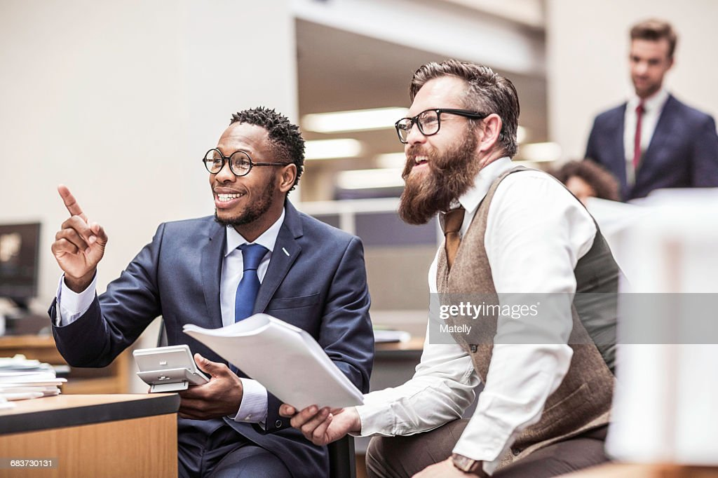 Two businessmen reading paperwork and pointing in office : Stock Photo