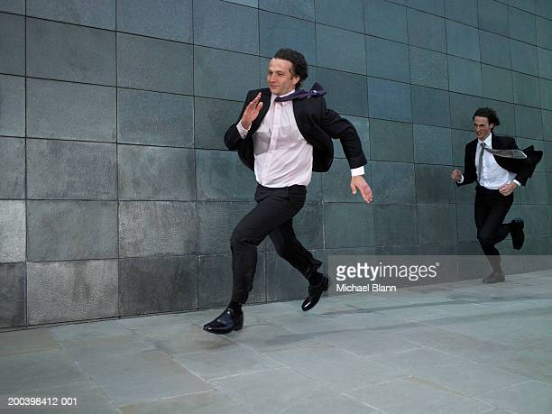 Two businessmen running against wind