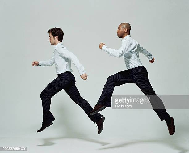 Two businessmen running, side view