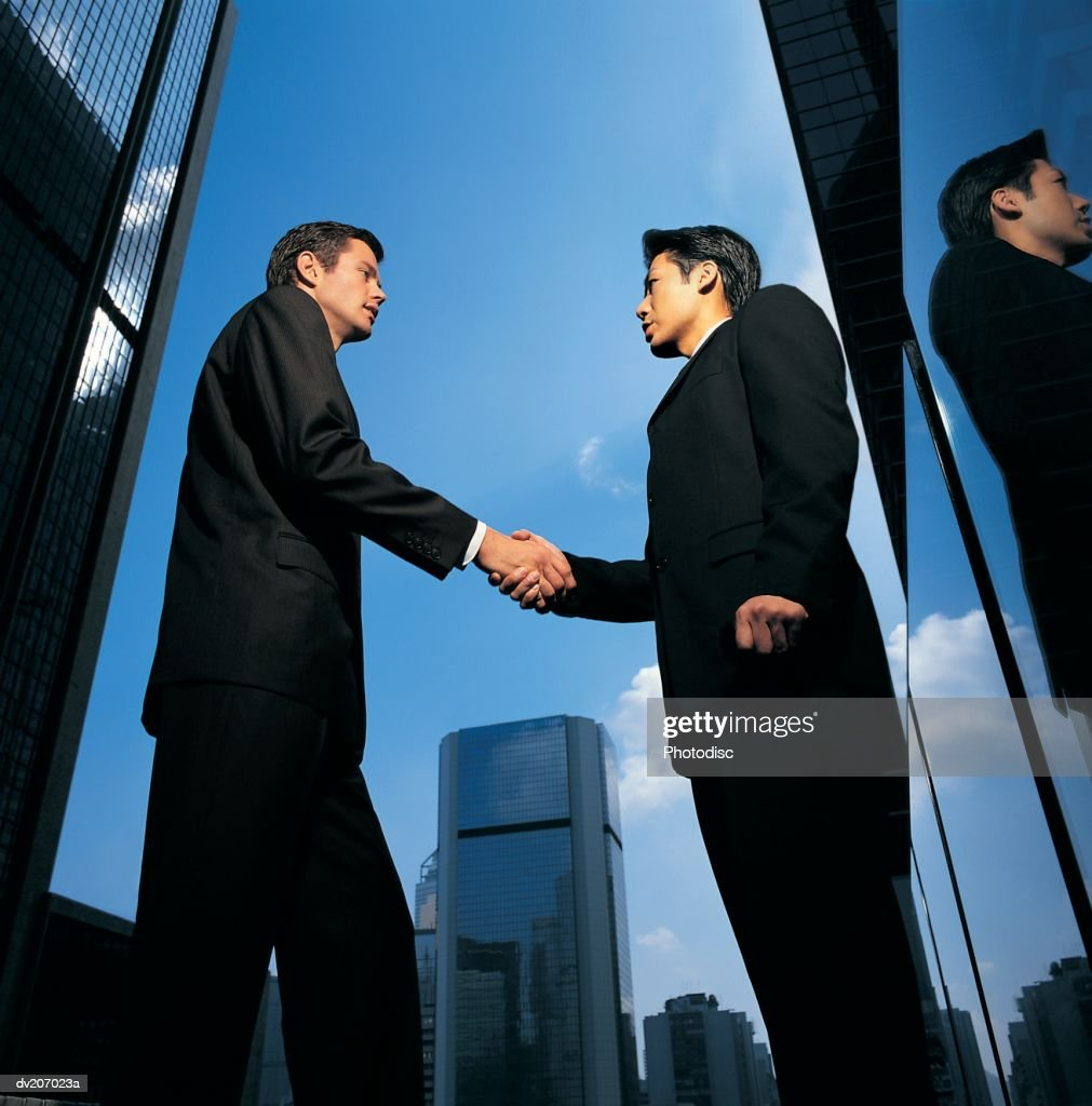 Two businessmen shaking hands among skyscrapers : Stock Photo