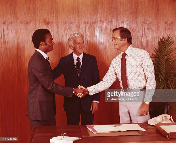 Two businessmen shaking hands at desk, executive looking on, smiling. (Photo by H. Armstrong Roberts/Retrofile/Getty Images)