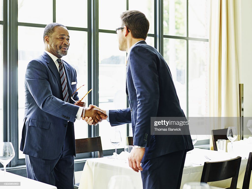 Two businessmen shaking hands at lunch meeting : Stock Photo