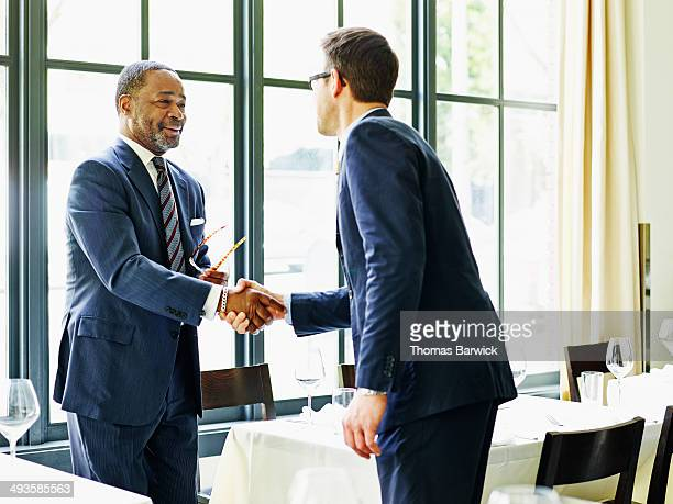 two businessmen shaking hands at lunch meeting - agreement stock pictures, royalty-free photos & images