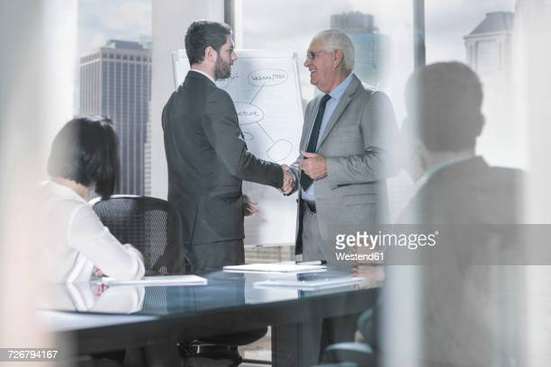 two businessmen shaking hands at office meeting - mid adult men fotografías e imágenes de stock