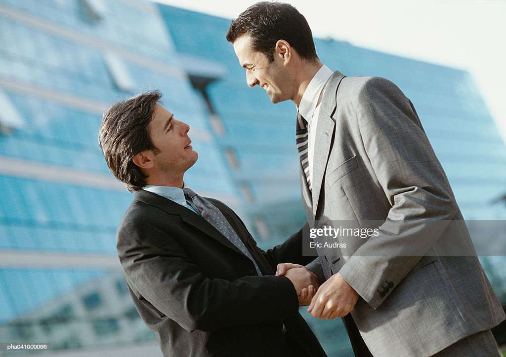 Two businessmen shaking hands, buildings in background : Stockfoto