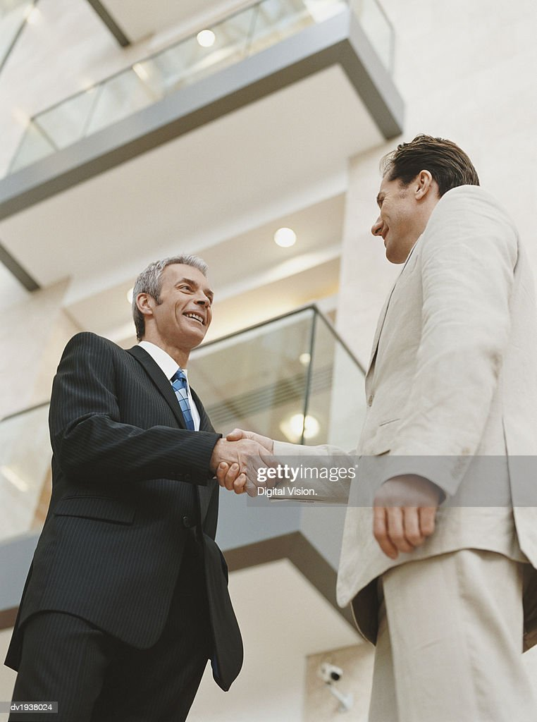 Two Businessmen Shaking Hands by an Office Building : Stock Photo