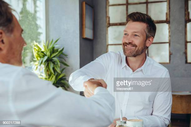 two businessmen shaking hands in cafe - truth be told stock photos and pictures