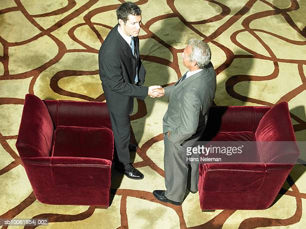 Two businessmen shaking hands in hotel lobby, elevated view