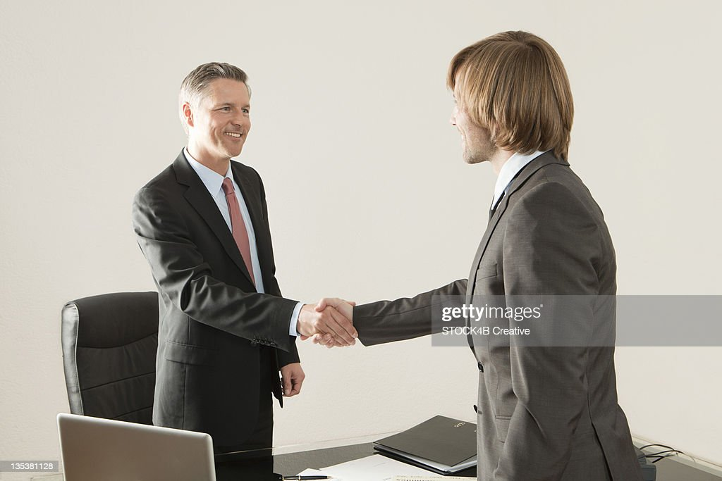 Two businessmen shaking hands in office : Stock Photo