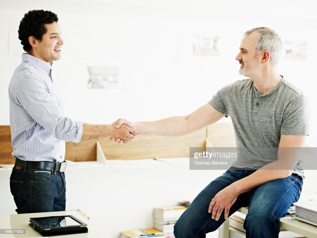 Two businessmen shaking hands in startup office : Stock Photo