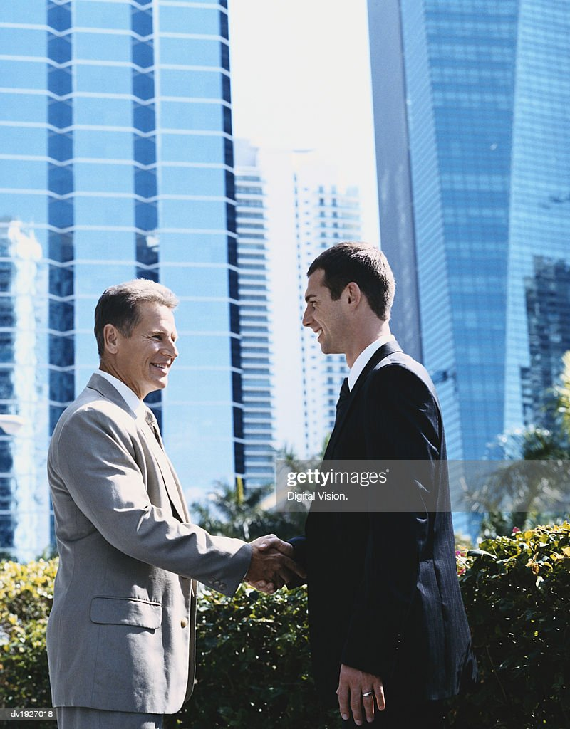 Two Businessmen Shaking Hands in the City : Stock Photo