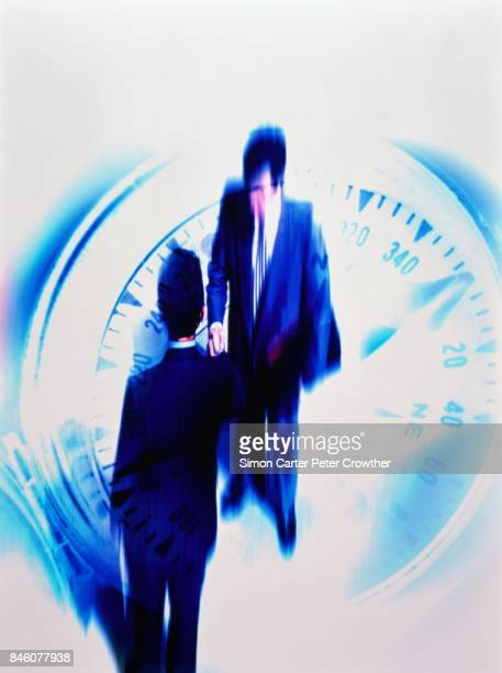 Two businessmen shaking hands on compass (Digital Composite)