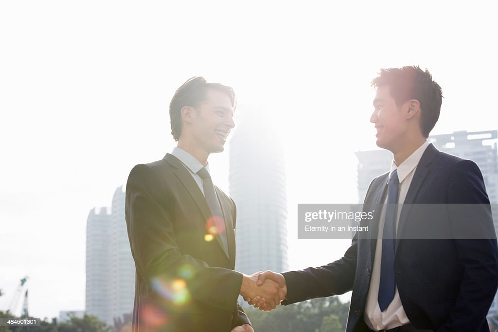 Two businessmen shaking hands outdoors. : Stock Photo