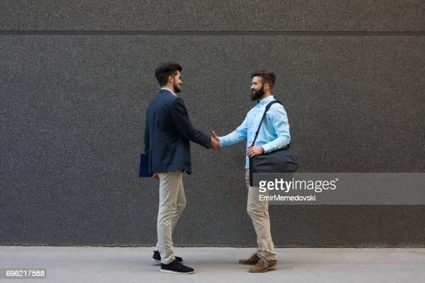 Zwei Geschäftsleute schütteln die Hände im Freien
