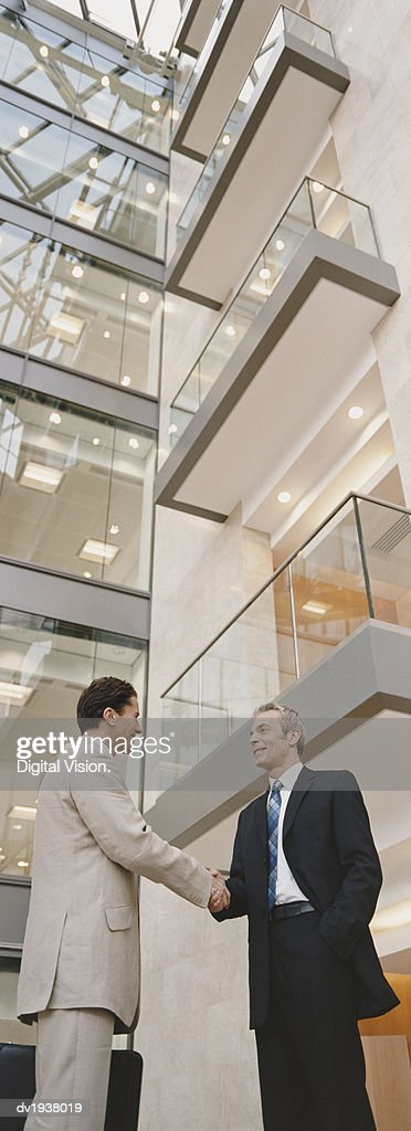Two Businessmen Shaking Hands Outside an Office Building : Stock Photo