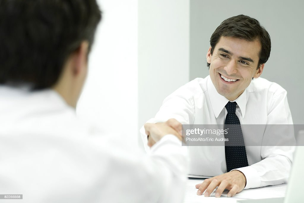 Two businessmen shaking hands, over the shoulder view : Stock Photo