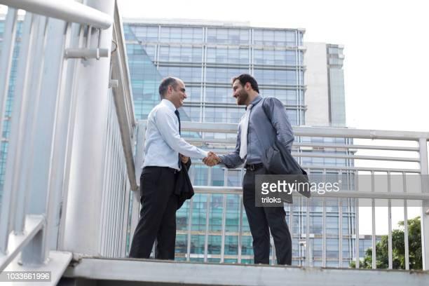 two businessmen shaking hands - dar cartas imagens e fotografias de stock