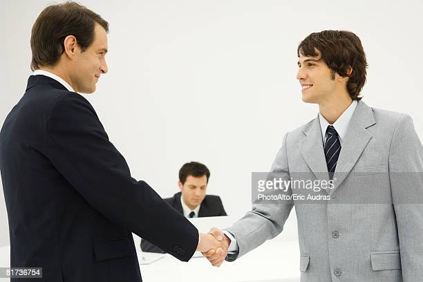 Two businessmen shaking hands, smiling at each other
