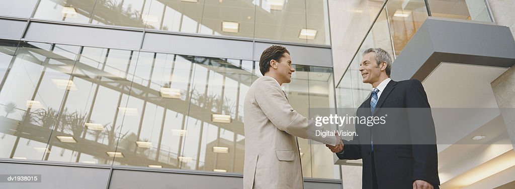 Two Businessmen Shaking Hands Standing Outside an Office Building : ストックフォト