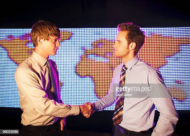 Two businessmen shaking hands, world map behind
