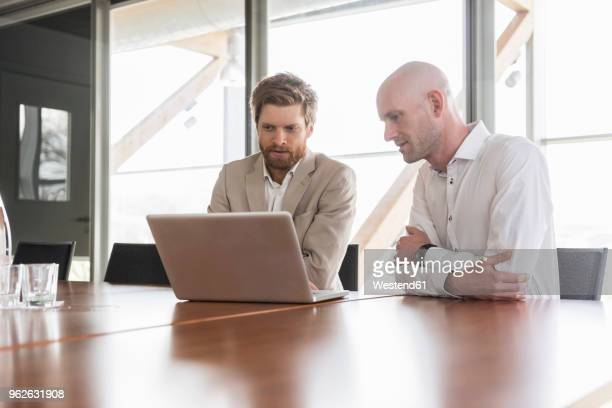 two businessmen sharing laptop in conference room - rat stock-fotos und bilder