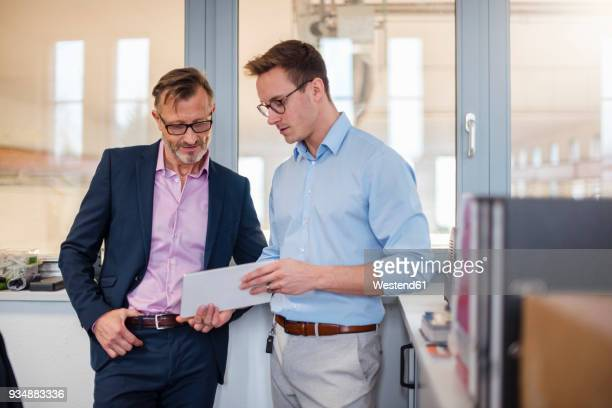 Two businessmen sharing tablet in office