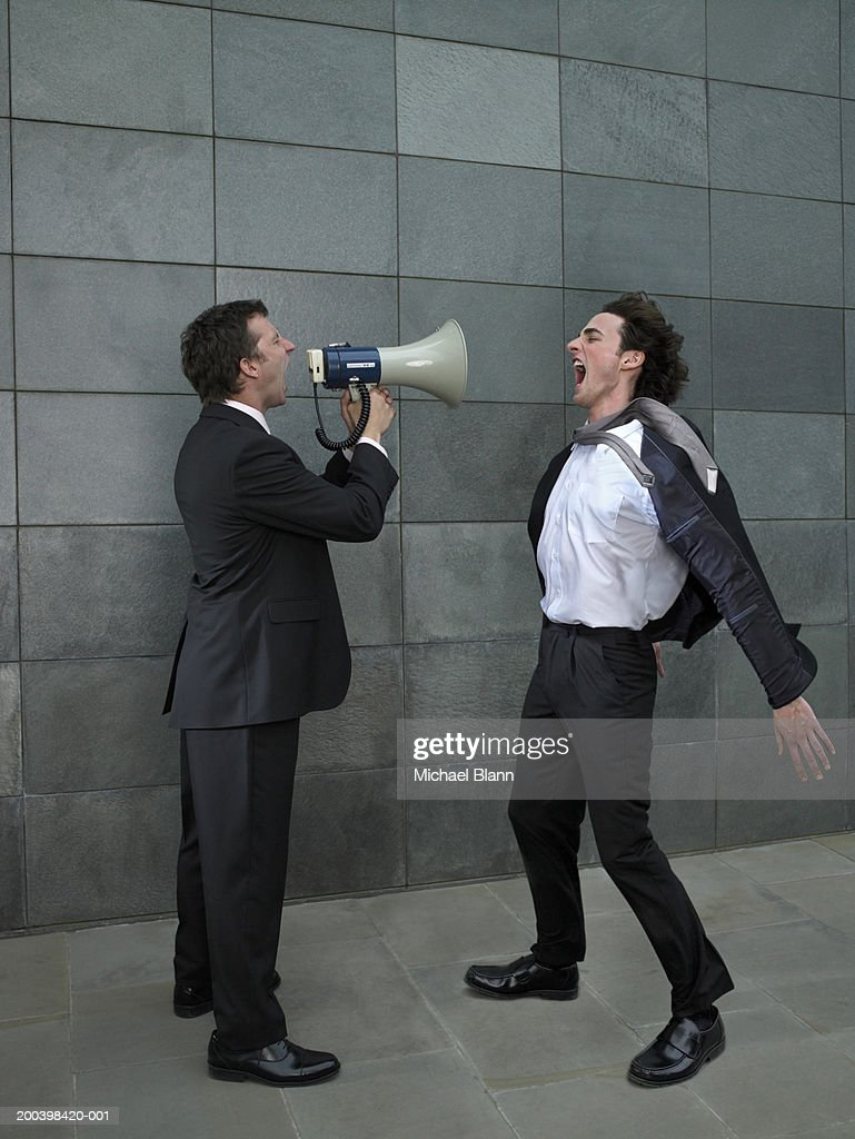 Two businessmen shouting at each other, one using megaphone, side view : Stock Photo