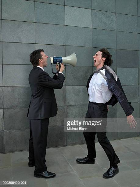 Two businessmen shouting at each other, one using megaphone, side view