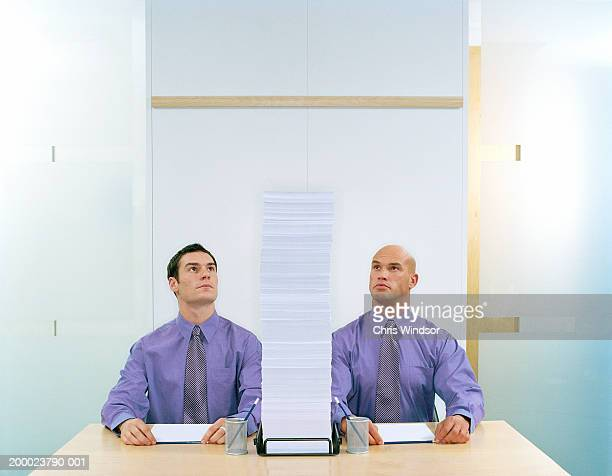 two businessmen side by side looking at stack of paper - side by side stock pictures, royalty-free photos & images