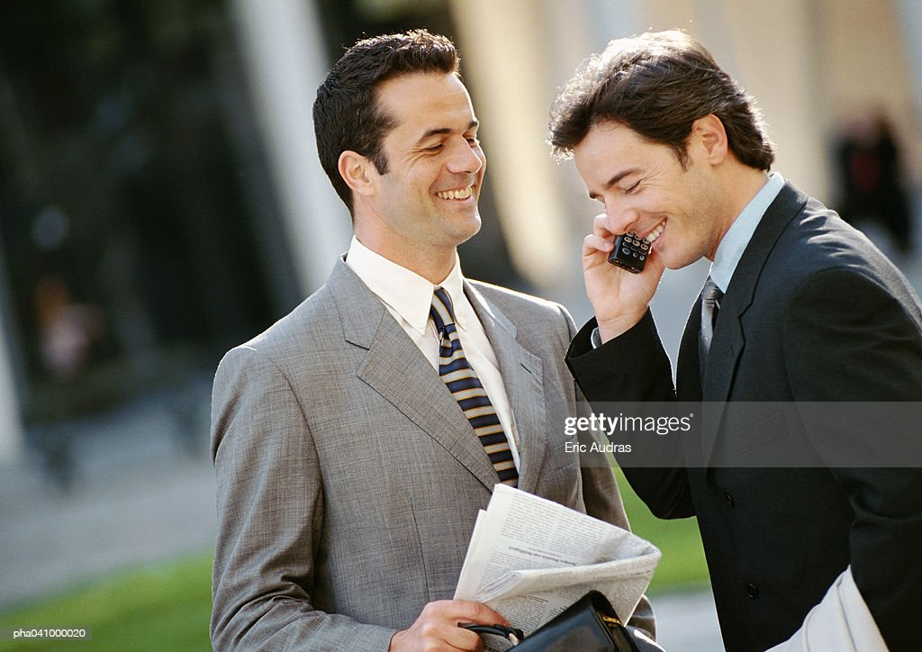 Two businessmen side by side outside, one using cell phone : Stockfoto