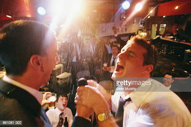 Two businessmen singing on stage in nightclub