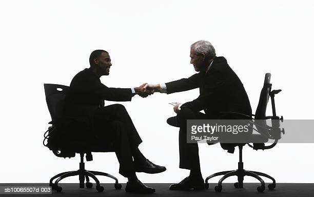 Two businessmen sitting and shaking hands, side view