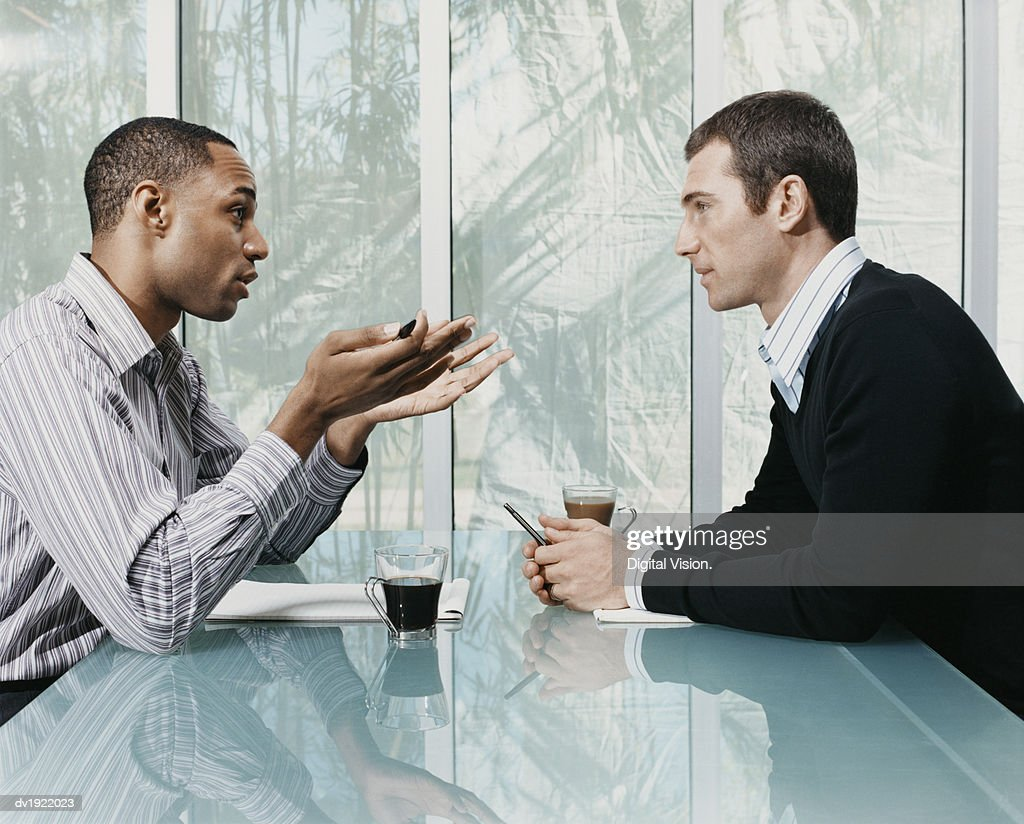 Two Businessmen Sitting and Talking Face to Face in a Meeting : Stock Photo