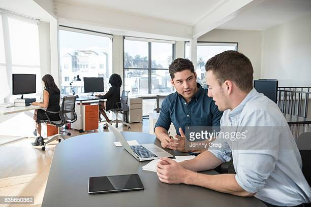 Two businessmen sitting at desk in office with laptop