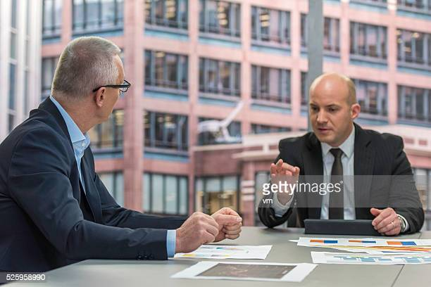 Two businessmen sitting behind a table and talking