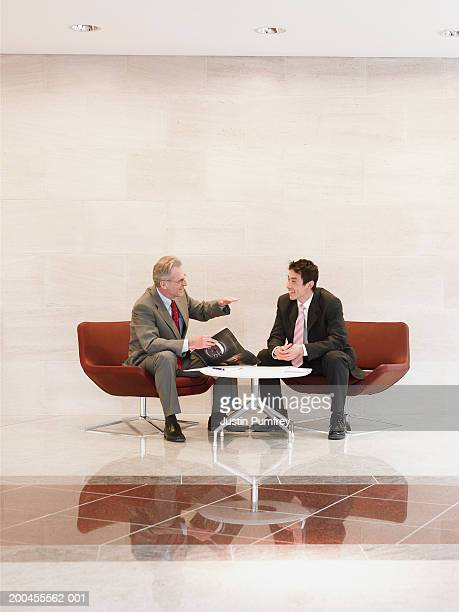 Two businessmen sitting by table talking