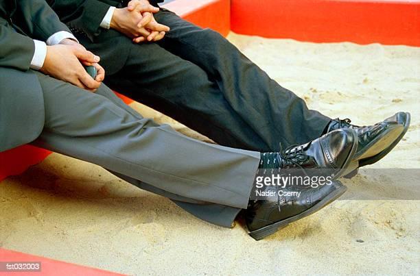 Two businessmen sitting in a sandbox