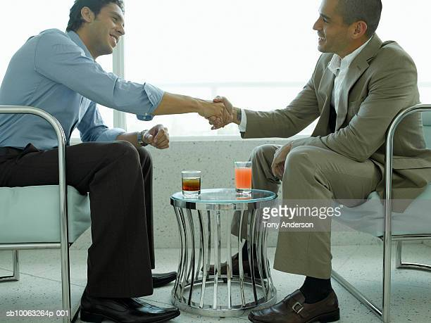 Two businessmen sitting in hotel lobby, shaking hands, side view